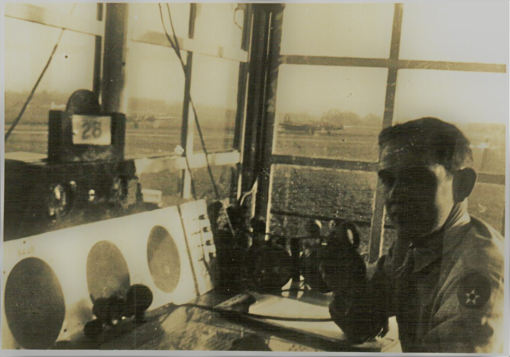 Man sitting at control tower radio overlooking flightline on WWII bomber base